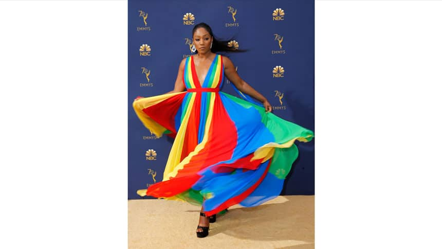 A woman twirls her dress for photographers on the gold carpet with a blue Emmys backdrop.