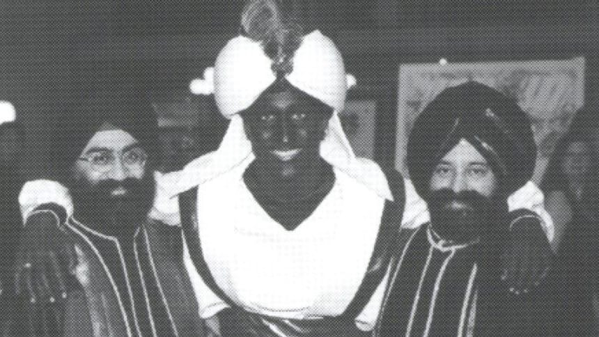 A man with his face painted brown in an Aladdin costumes poses with his arms around 2 Sikh men