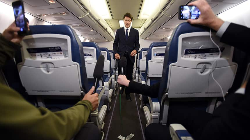A man in a suit walks to the back of a plane.