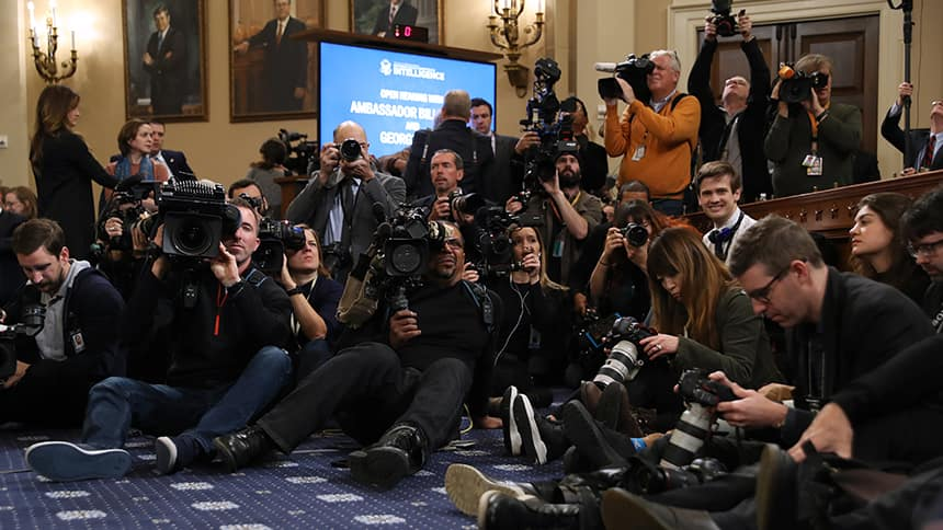 Journalists, camera-operators and photographers sit together in on the floor of a room