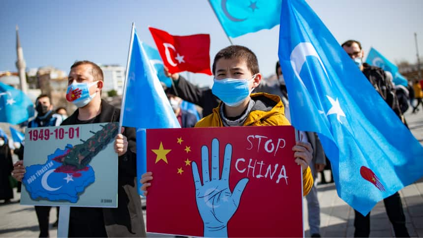 Boy wearing mask holds sign that says Stop China