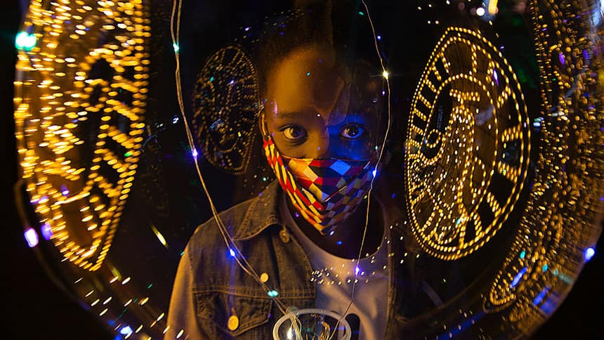 Kid in mask surrounded by Christmas lights.