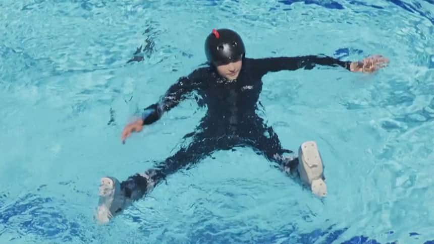 Girl in ski boots on floats in pool.