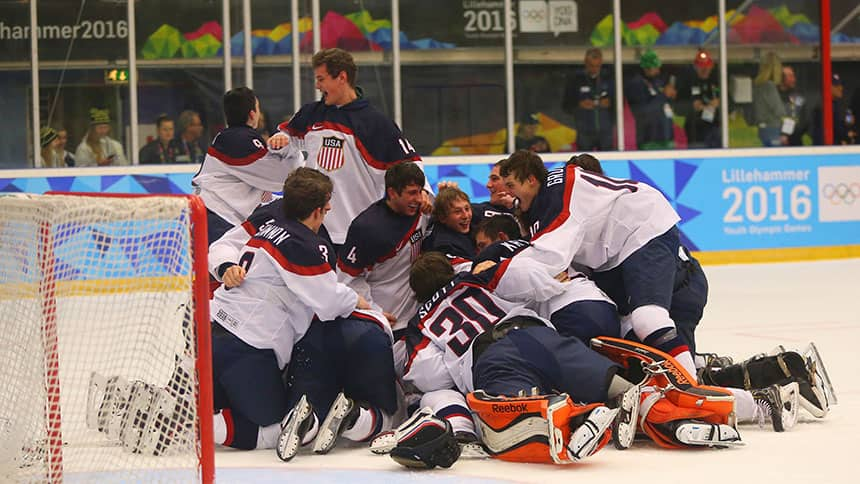 US boys hockey team celebrates on the ice by piling onto their goalie.