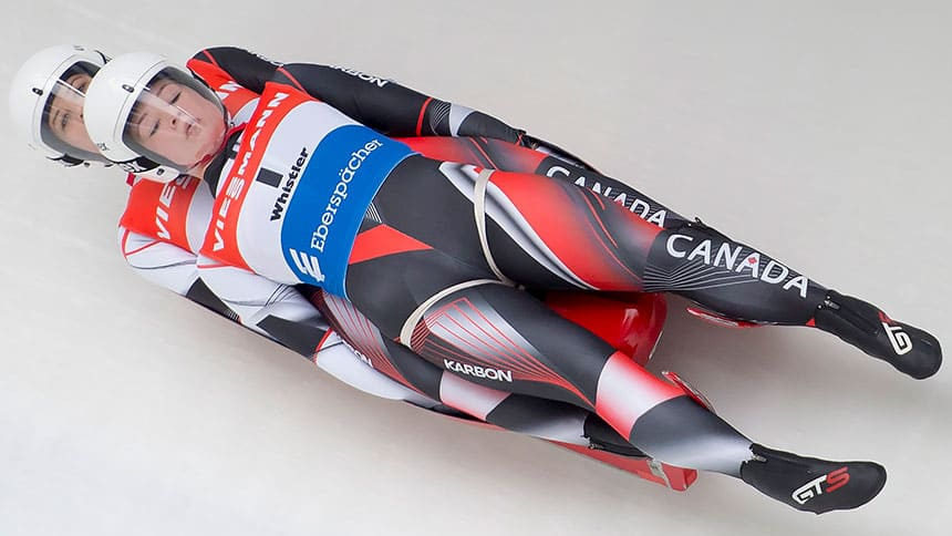 Two lugers on their backs on a luge, one is stacked on top of the other with their bodies rigid, both are wearing helmets and Canada bodysuits, as they race down an ice track.