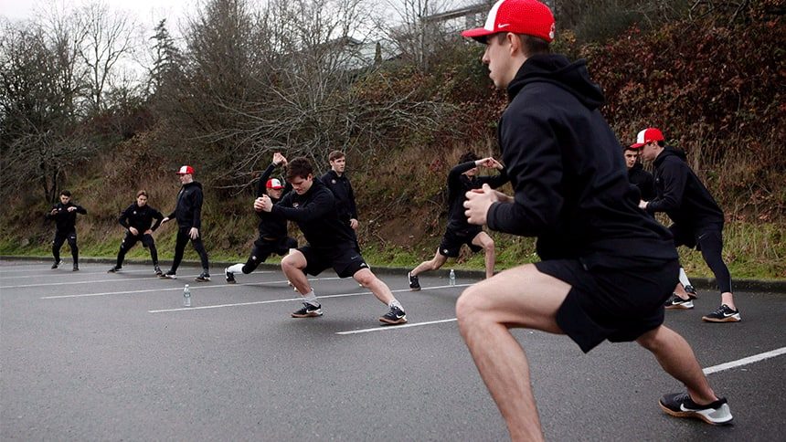 Hockey players stretch in a parking lot