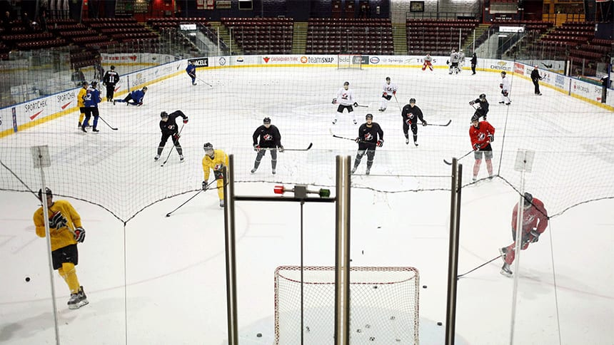 hockey players take shots on an empty net.