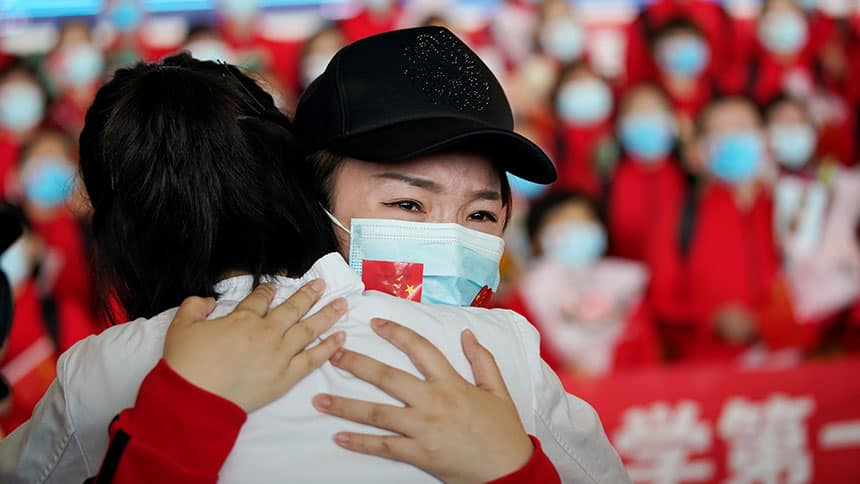 Emotional woman in mask gives a big hug.