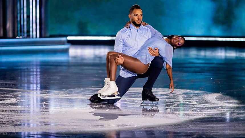 A male and female figure skating team perform an ice dance move.