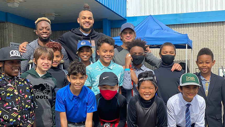 Akim Aliu poses with a group of kids from his BIPOC youth hockey team in front of an arena.
