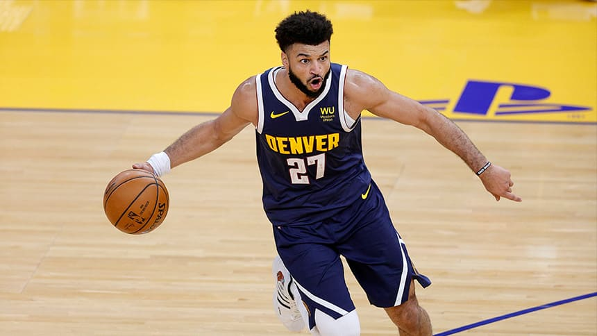 Basketball player Jamal Murray dribbles and points