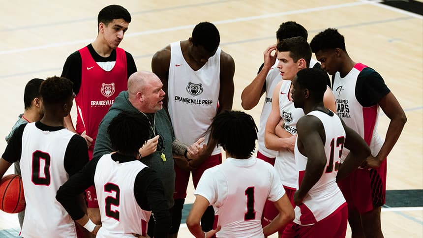 A coach is surrounded by basketball players at practice while he gives instructions