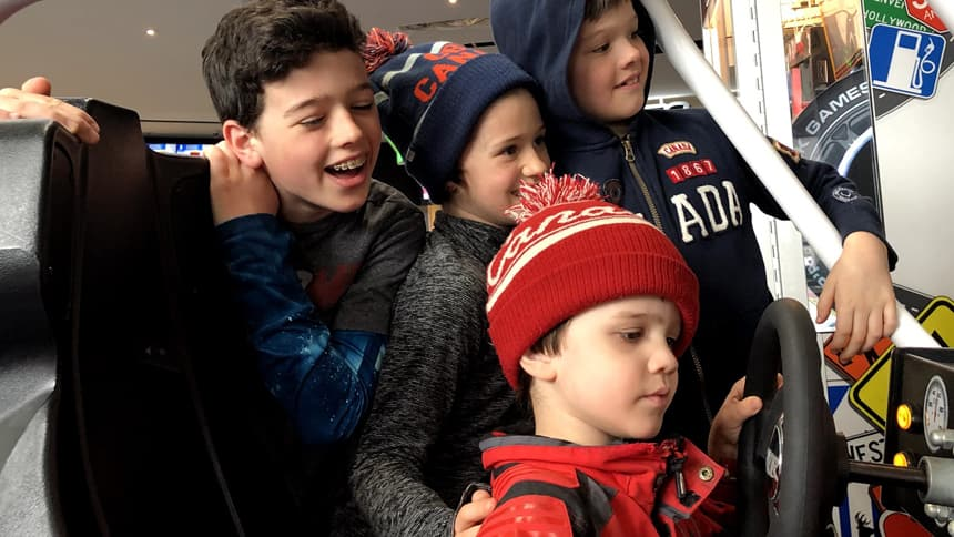 Four siblings playing an arcade game, laughing and smiling.