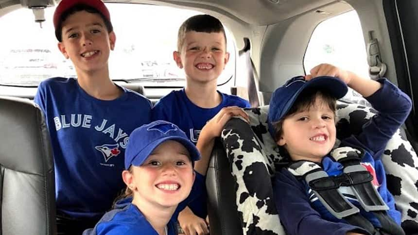 Four kids sit in a car, smiling broadly, wearing matching Blue Jays gear