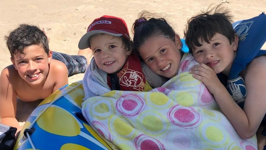 Four siblings smiling on a beach.