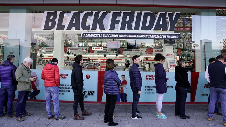A line up of people in front a sign on a store that says Black Friday