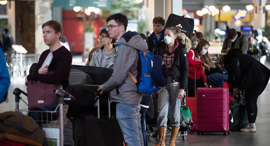 Travellers wait in a lineup to check-in for a flight. One traveller is wearing a mask.