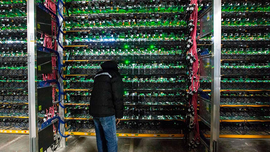 A man inspects shelves of computers in a warehouse.