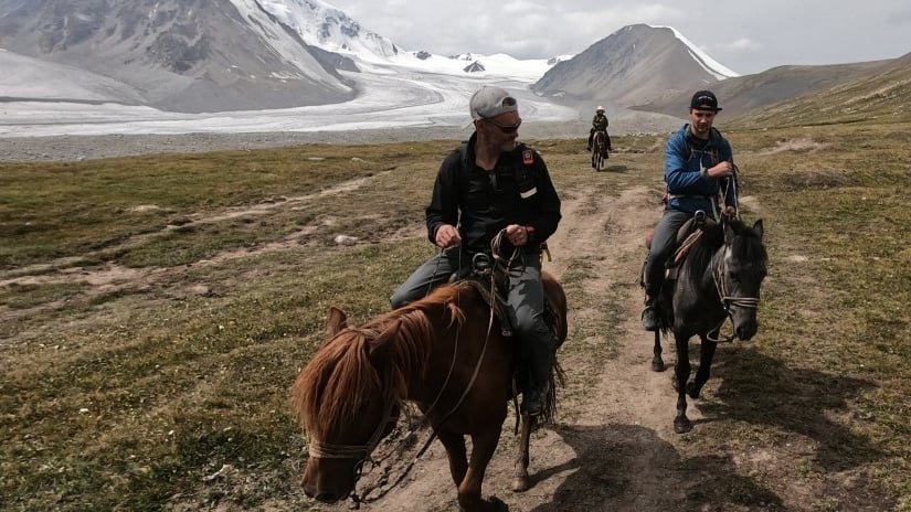 Khobe, right, and his dad riding horses in front of Mount Khüiten in Mongolia.