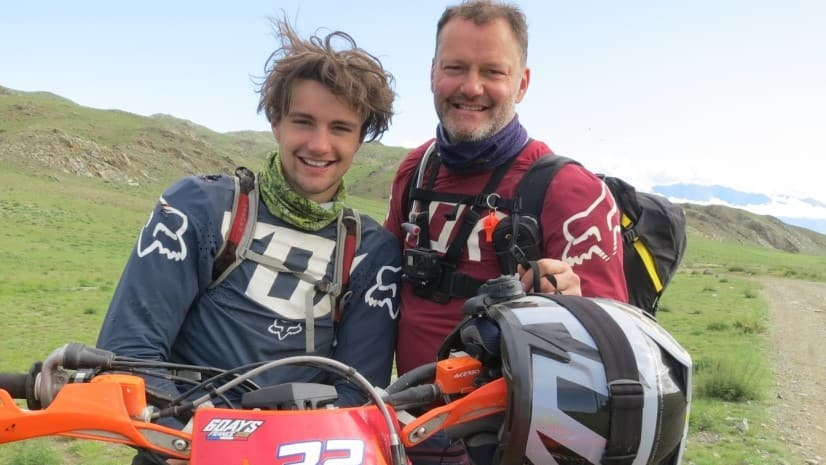 Khobe and Jamie smiling together on their motorcycles.