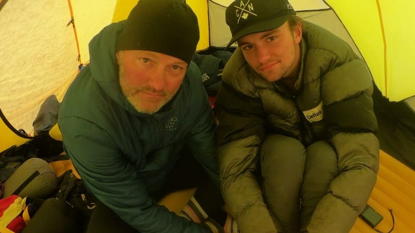 Khobe, right, and Jamie sitting in their tent surrounded by camping gear.