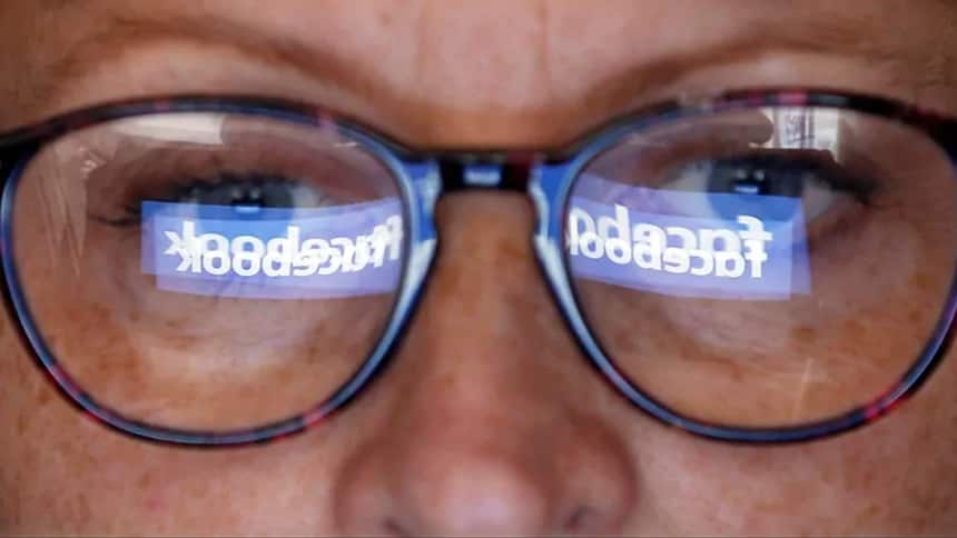 person looking at computer with Facebook reflected in their glasses