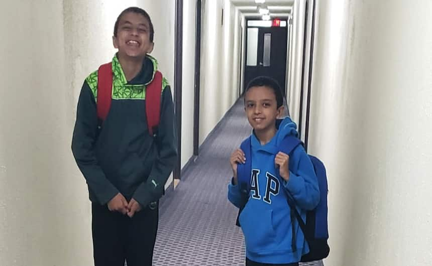 Mohamed and Mohab Ahmed stand, beaming, in a hallway wearing backpacks