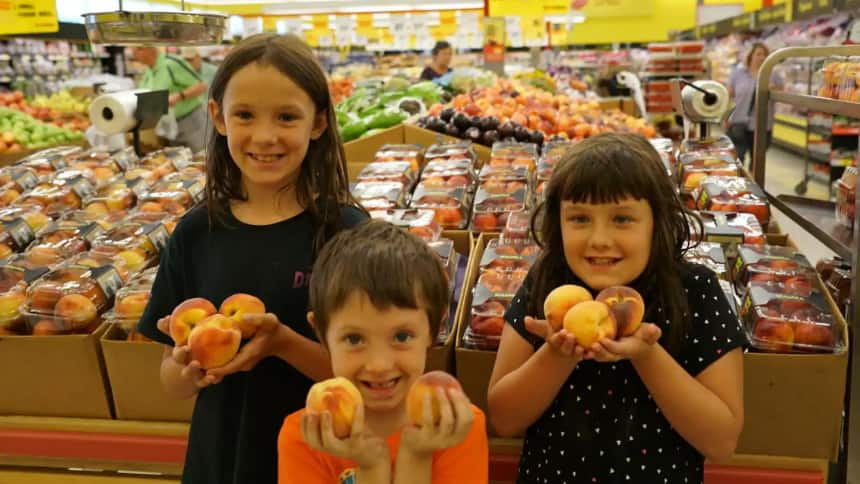 Three children stand in a grocery store holding peaches