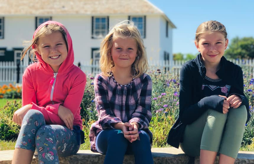 From left to right: Sisters Morgan, Linnea and Brooklyn Harder smiling together on steps in front of a house.