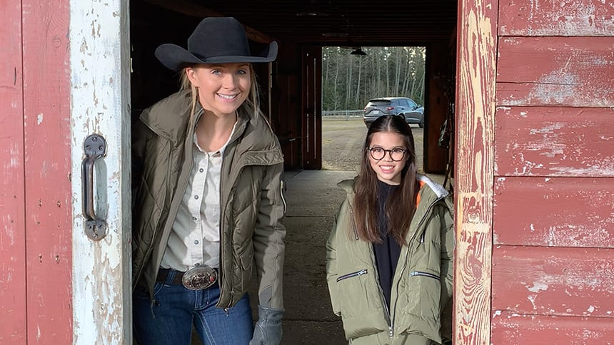 A woman and a young girl pose int he opening of a barn door, smiling.
