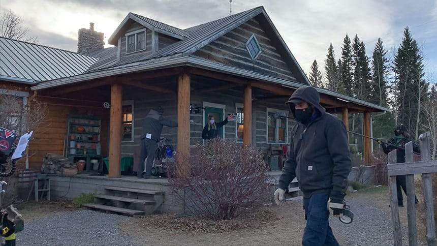 A film crew busy at work preparing for a shot in front of a ranch style home in Alberta.