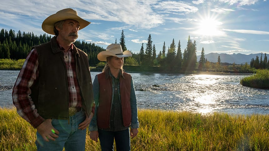 Heartland characters Grandpa Jack and Amy stand together on a river bank, looking serious as the sun sets.