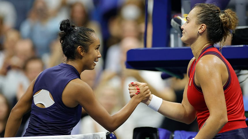 Fernandez greets her opponent at the net as they shake hands.