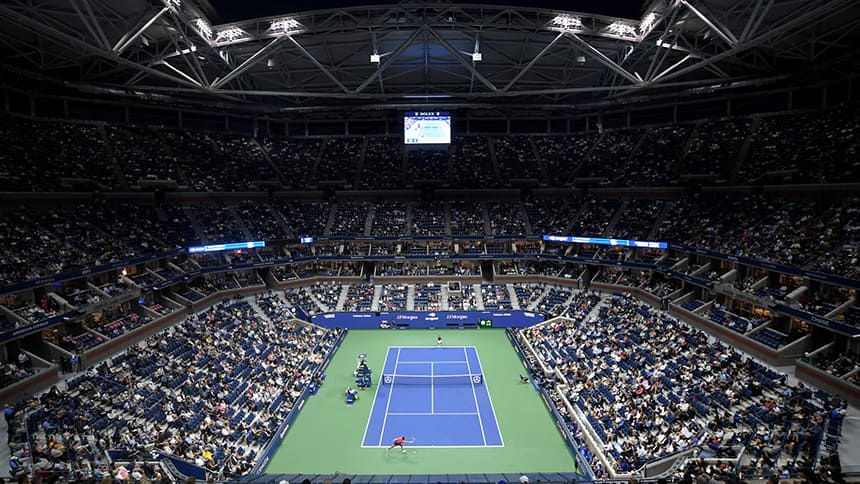 A wide shot of the main tennis court in New York during a night match under the lights.