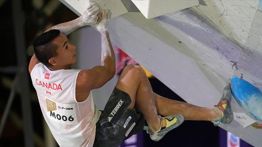 a sport climber hangs off of an indoor climbing wall