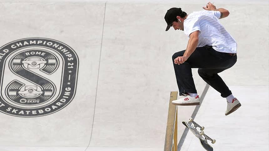 A man flips his skateboard under his feet while in mid-air.