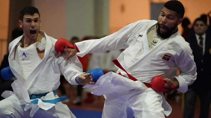 Two men dressed in Karate outfits spar in a match