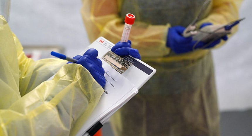A person wearing personal protective equipment holding a test tube and a clipboard