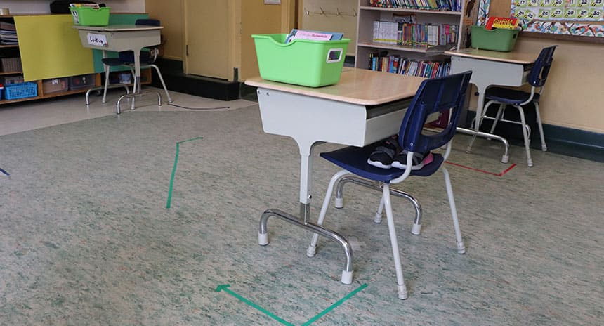 desks in a classroom with tapes marked on the floor to keep them apart.