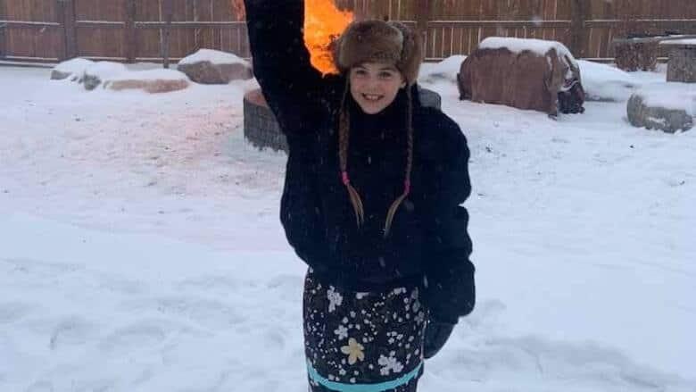 Isabella Kulak raises her fist in pride wearing her ribbon skirt