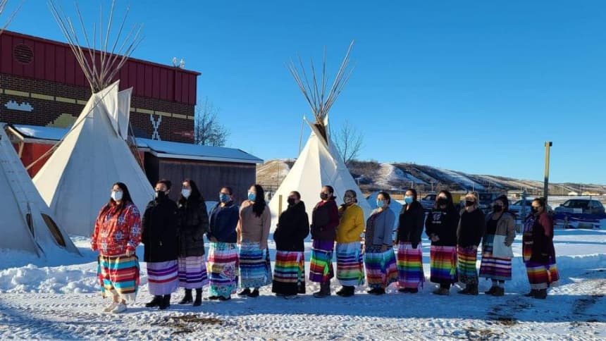 A line of Indigenous women in wearing colourful ribbon skirts in the snow