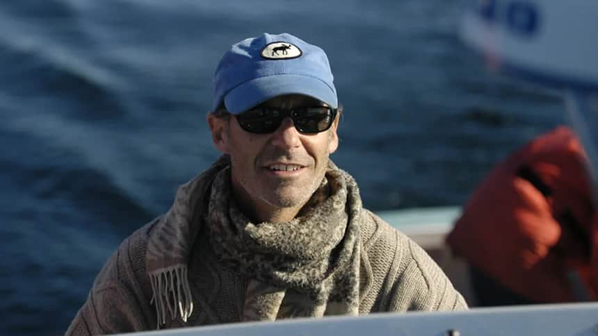 A close-up of a scientist in a ball cap and shades looking out over the water.