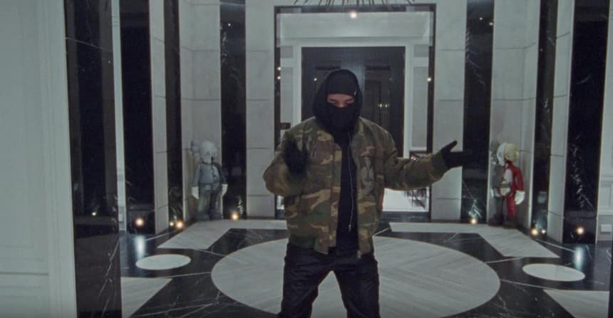 Drake dancing and rapping in his home. His face is covered and he is wearing black gloves.