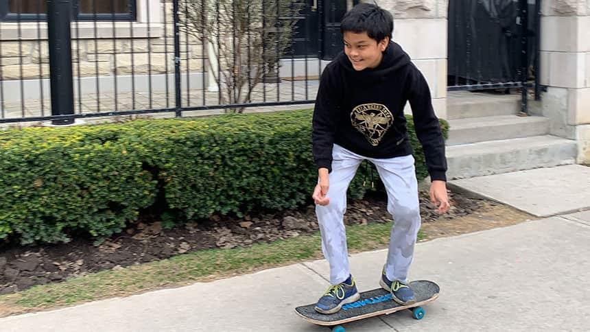 A kid skateboards down the street