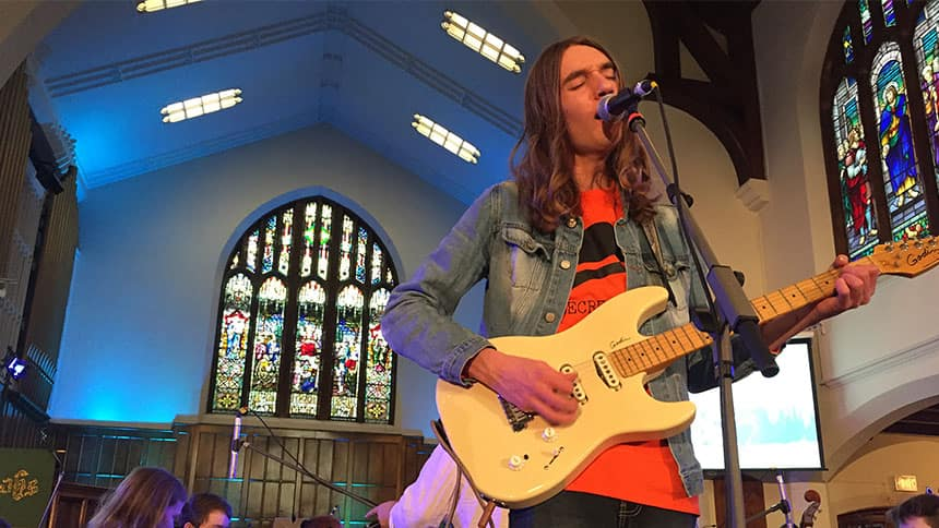 A teenager plays guitar and sings in front of an orchestra in a church