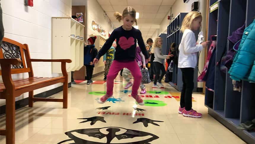 A girl jumps along a painted floor path