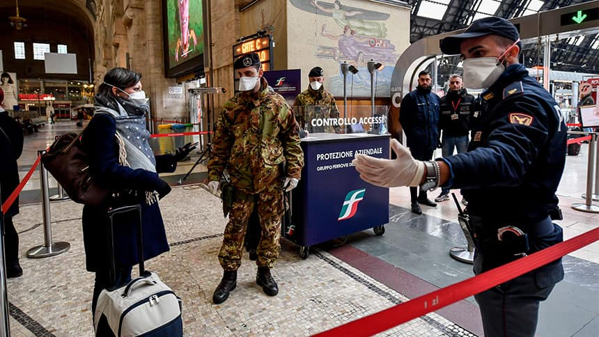 A woman carrying a suitcase is stopped by police in a train station. Everyone is wearing a mask.