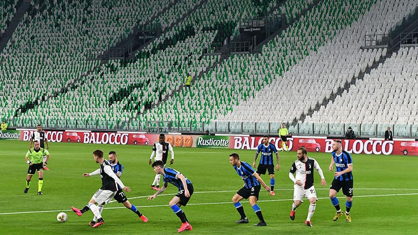 Professional soccer players in front of empty seats in a stadium.
