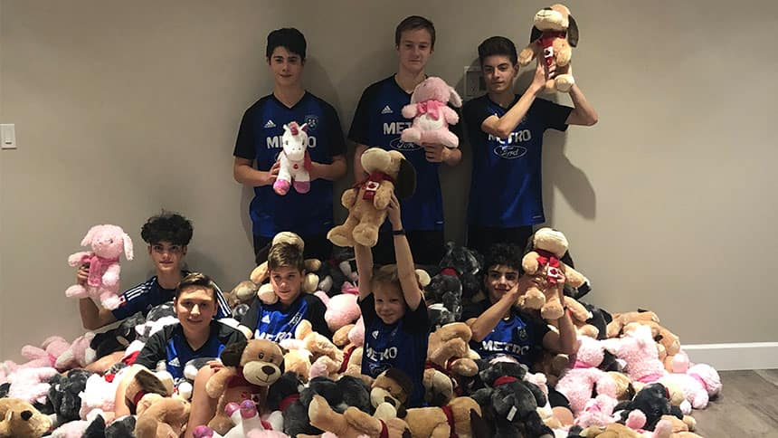 A group of boys in soccer jerseys surrounded by stuffies