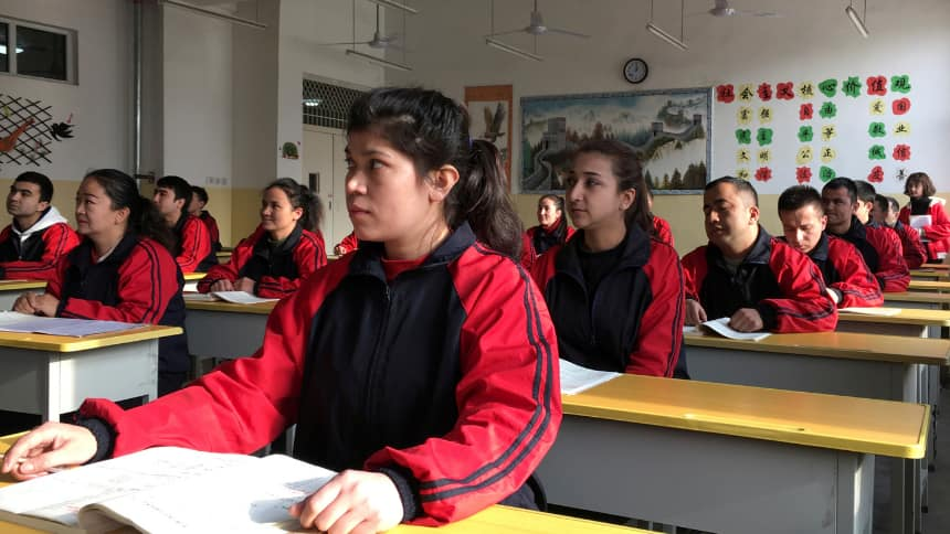 Uyghur men and women in matching jackets sit at desks in a classroom